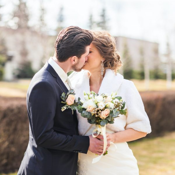bride-and-groom-kissing-on-their-wedding-day-outdoors.jpg